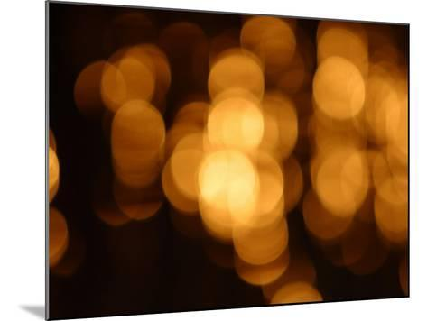 Blurry Orange Lights Illuminating Against a Black Background--Mounted Photographic Print