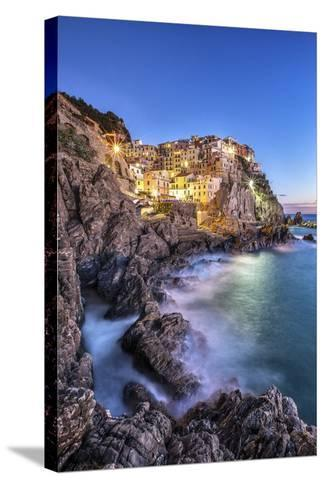 Manarola Village Illuminated by the Blue Light of Dusk with its Typical Pastel Colored Houses-ClickAlps-Stretched Canvas Print