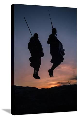 Two Masaai Warriors Silhouetted Performing Traditional Jump - Leap Kopje at Sunset-Nick Garbutt-Stretched Canvas Print