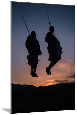 Two Masaai Warriors Silhouetted Performing Traditional Jump - Leap Kopje at Sunset-Nick Garbutt-Mounted Photographic Print