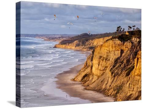 USA, California, La Jolla. Paragliders Float over Black's Beach in Late Afternoon-Ann Collins-Stretched Canvas Print