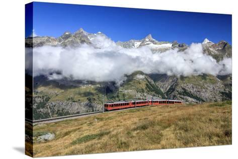 The Bahn Train on its Route with High Peaks and Mountain Range in the Background, Switzerland-Roberto Moiola-Stretched Canvas Print