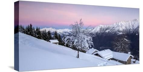 Pink Sky at Dawn Above Snow Covered Huts and Trees, Orobie Alps-Roberto Moiola-Stretched Canvas Print