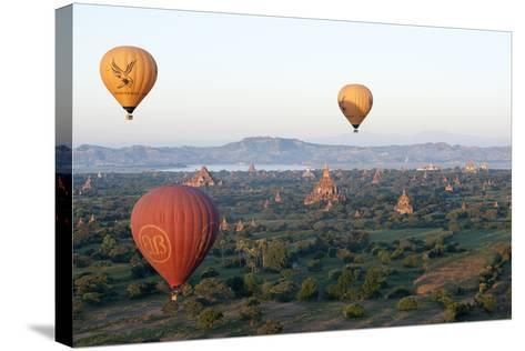 Hot Air Balloons Flying over the Terracotta Temples of Bagan-Annie Owen-Stretched Canvas Print