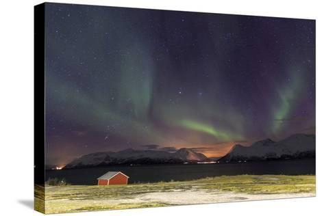 Northern Lights Illuminates the Wooden Cabin at Svensby, Lyngen Alps, Troms, Lapland, Norway-Roberto Moiola-Stretched Canvas Print