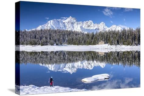 Hiker Admires the Snowy Peaks and Woods Reflected in Lake Palu, Malenco Valley, Valtellina, Italy-Roberto Moiola-Stretched Canvas Print