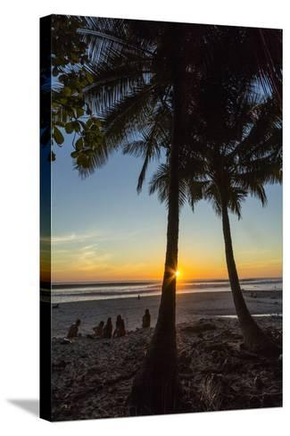 People by Palm Trees at Sunset on Playa Hermosa Beach, Santa Teresa, Costa Rica-Rob Francis-Stretched Canvas Print