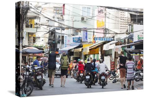 Backpackers on City Street, Ho Chi Minh City (Saigon), Vietnam, Indochina, Southeast Asia, Asia-Christian Kober-Stretched Canvas Print