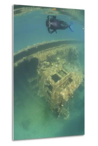 A Snorkeler Swims Above a Shipwreck in Palau's Inner Lagoon-Stocktrek Images-Metal Print