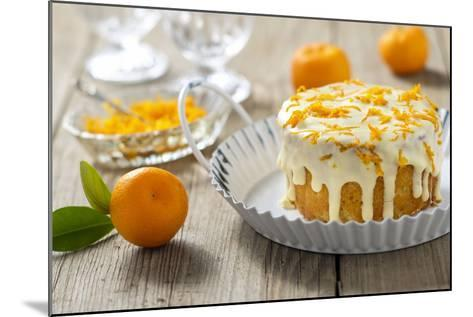 Small Orange Cake with White Icing on Wooden Table-Jana Ihle-Mounted Photographic Print