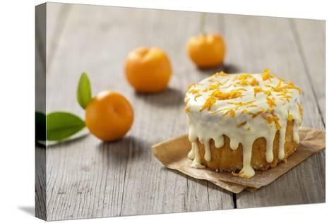Small Orange Cake with White Icing on Wooden Table-Jana Ihle-Stretched Canvas Print
