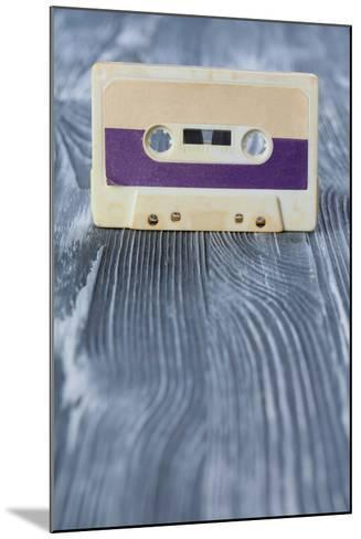 Music Template Postcard. Violet Audio Cassette on the Gray Wooden Background. Vintage, Retro Style.-Besjunior-Mounted Photographic Print