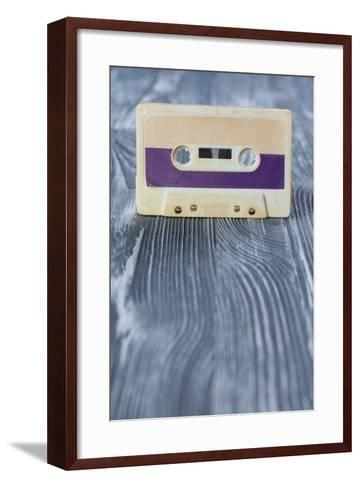 Music Template Postcard. Violet Audio Cassette on the Gray Wooden Background. Vintage, Retro Style.-Besjunior-Framed Art Print