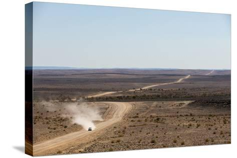 A Car Leaves a Cloud of Dust as it Apporachs Along the Long Dusty Road from the Fish River Canyon-Alex Treadway-Stretched Canvas Print