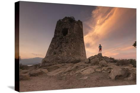 Hiker Admires Sunset from the Stone Tower Overlooking the Bay, Porto Giunco, Villasimius-Roberto Moiola-Stretched Canvas Print