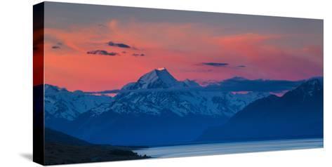 The Last Rays of Setting Sun Strike Peak of Aoraki (Mount Cook) Beyond Shores of Lake Pukaki-Garry Ridsdale-Stretched Canvas Print