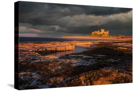 A Storm Passes Behind Bamburgh Castle with Last Light of Day Illuminating Rocky Shoreline-Garry Ridsdale-Stretched Canvas Print