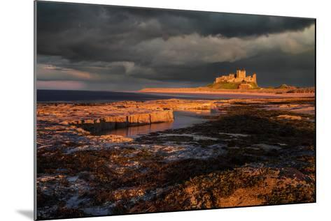 A Storm Passes Behind Bamburgh Castle with Last Light of Day Illuminating Rocky Shoreline-Garry Ridsdale-Mounted Photographic Print