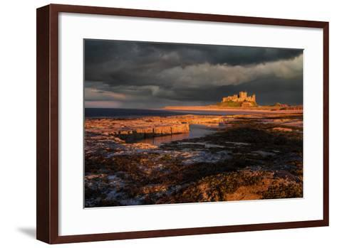 A Storm Passes Behind Bamburgh Castle with Last Light of Day Illuminating Rocky Shoreline-Garry Ridsdale-Framed Art Print
