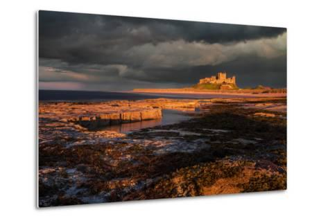 A Storm Passes Behind Bamburgh Castle with Last Light of Day Illuminating Rocky Shoreline-Garry Ridsdale-Metal Print