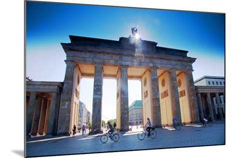 Germany, Berlin. Cyclists Passing under the Brandenburg Gate-Ken Scicluna-Mounted Photographic Print