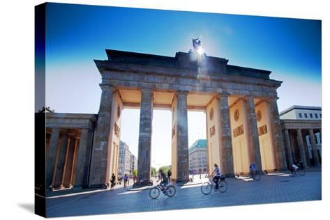 Germany, Berlin. Cyclists Passing under the Brandenburg Gate-Ken Scicluna-Stretched Canvas Print