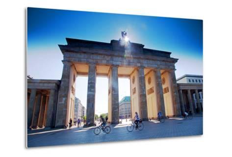 Germany, Berlin. Cyclists Passing under the Brandenburg Gate-Ken Scicluna-Metal Print