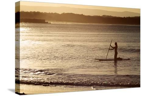 A Woman on a Stand-Up Paddleboard Heads Towards Main Beach, Noosa, at Sunset-William Gray-Stretched Canvas Print