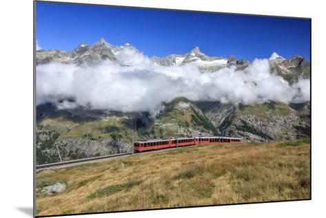 The Bahn Train on its Route with High Peaks and Mountain Range in the Background, Switzerland-Roberto Moiola-Mounted Photographic Print