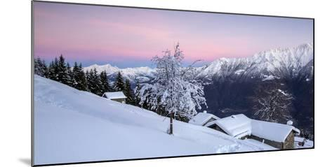 Pink Sky at Dawn Above Snow Covered Huts and Trees, Orobie Alps-Roberto Moiola-Mounted Photographic Print