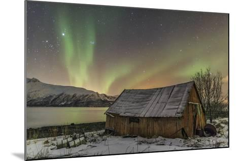 The Northern Lights Illuminates the Wooden Cabin, Svensby, Lyngen Alps, Troms, Lapland, Norway-Roberto Moiola-Mounted Photographic Print