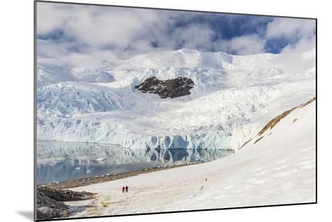 Two Hikers Surrounded by Ice-Capped Mountains and Glaciers in Neko Harbor, Polar Regions-Michael Nolan-Mounted Photographic Print