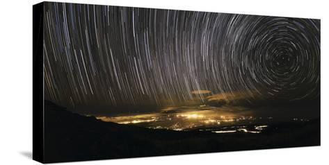 Time-Exposure Image of Star Trails Above a Town on Maui, Hawaii-Babak Tafreshi-Stretched Canvas Print