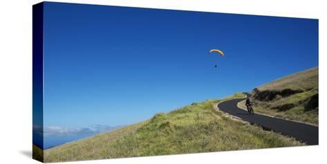 A Paraglider Soars Above a Mountain Biker-Chad Copeland-Stretched Canvas Print
