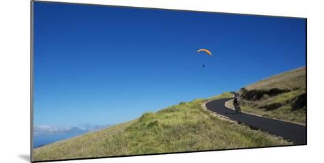 A Paraglider Soars Above a Mountain Biker-Chad Copeland-Mounted Photographic Print