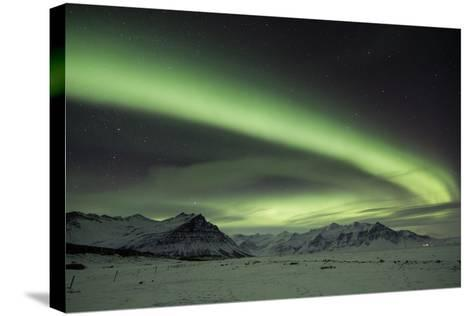 The Aurora Borealis in Iceland with Mountains in the Background-Alex Saberi-Stretched Canvas Print
