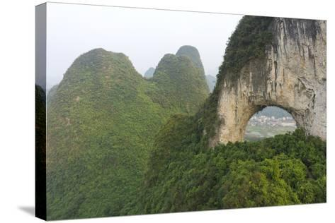 Climber on Natural Arch Formed at Moon Hill, Yangshuo, Guangxi Province, China-Chad Copeland-Stretched Canvas Print