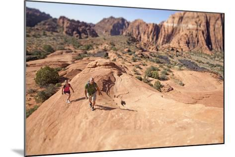 A Man and Woman Hiking in Snow Canyon State Park, Utah-John Burcham-Mounted Photographic Print