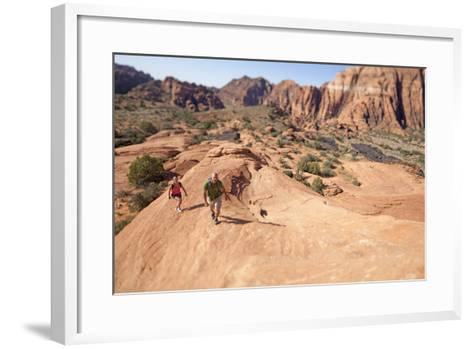 A Man and Woman Hiking in Snow Canyon State Park, Utah-John Burcham-Framed Art Print