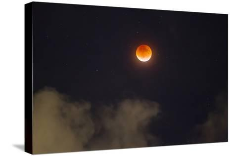 A Break in the Clouds Reveals a Rare Lunar Eclipse, also known as the Super Moon-Mike Theiss-Stretched Canvas Print