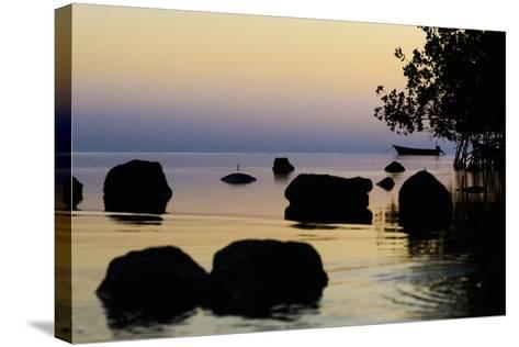 A Lone Fishing Boat Is Anchored at Sunset Near a Mangrove Forest on Molokai-Jonathan Kingston-Stretched Canvas Print