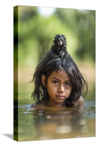 A Pet Saddleback Tamarin Hangs on Tight to a Matsigenka Girl as She Swims in the Yomibato River-Charlie Hamilton James-Stretched Canvas Print