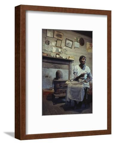 Woman with Cotton Stalks Beside a Wood-Burning Stove, Edisto Island, South Carolina, 1956-Walter Sanders-Framed Art Print