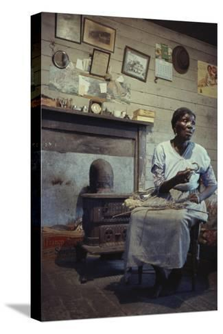 Woman with Cotton Stalks Beside a Wood-Burning Stove, Edisto Island, South Carolina, 1956-Walter Sanders-Stretched Canvas Print