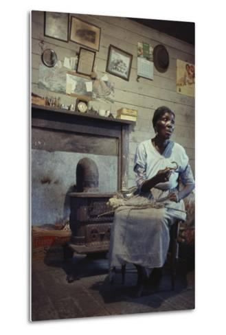 Woman with Cotton Stalks Beside a Wood-Burning Stove, Edisto Island, South Carolina, 1956-Walter Sanders-Metal Print