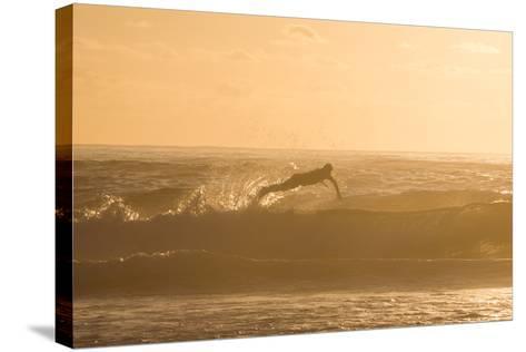 A Surfer Dives over a Wave on Praia Da Joaquina Beach on Florianopolis Island-Alex Saberi-Stretched Canvas Print