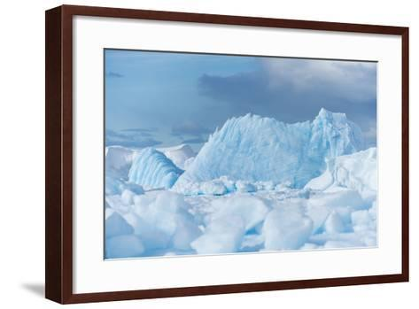 Blue Iceberg Floats Amidst Sea Ice in Fournier Bay, Antarctica-Jeff Mauritzen-Framed Art Print