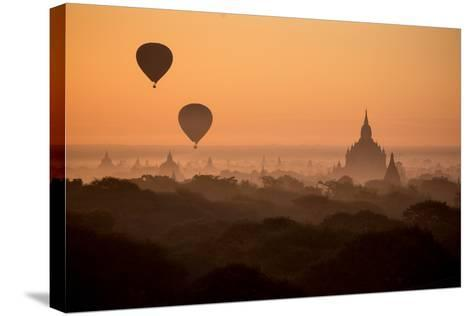 Hot Air Balloons Float Above the Terraces of a Buddhist Temple in Bagan-Cory Richards-Stretched Canvas Print