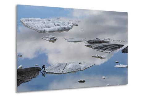 A Tourist Jumps onto an Iceberg from Hoffellsjokull Glacier in Vatnajokull, Iceland-Michael Melford-Metal Print