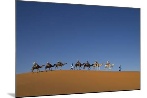 Morocco, Sahara. a Row of Camels Travels the Ridge of a Sand Dune-Brenda Tharp-Mounted Photographic Print